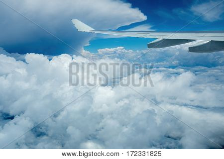 Sydney, Australia - Oct 29, 2016: Plane flying above fluffy clouds, not long after leaving Sydney Kingsford-Smith International Airport.
