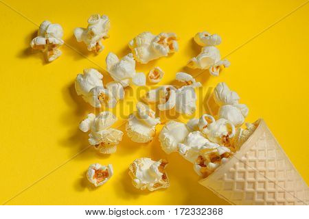 Popcorn in ice cream cones on yellow background