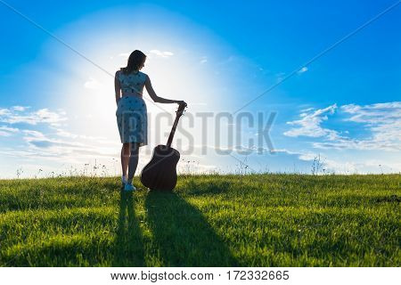 Woman In Dress Holding The Guitar On Cloudy Sunset Sky