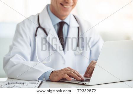 Cropped image of handsome mature doctor using a laptop and smiling while working in his office