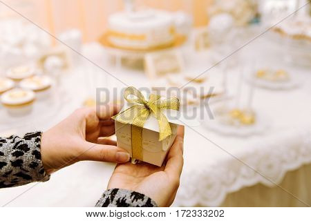 Wedding Bonbonniere with gold ribbon in hands