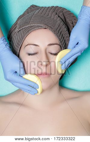 doctor beautician cleanses the skin woman with a sponge. Perfect cleaning - cosmetology treatment skincare face. Spa procedures