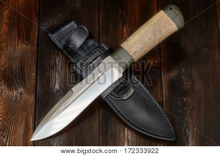 Hunting steel knife handmade and leather sheath on a brown wooden background closeup
