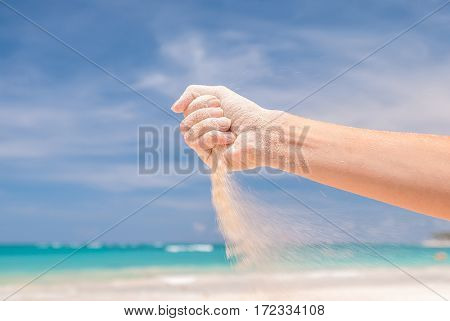 White sand strewing from hand