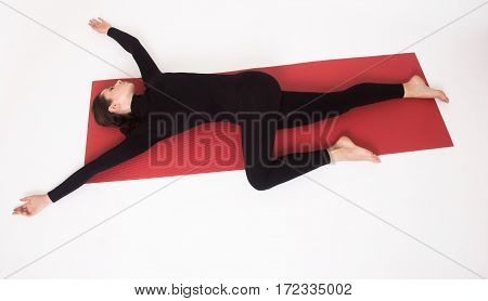 Beautiful athletic girl in a black suit doing yoga. Ardha Parivritta Nakrasana . Isolated on white background.
