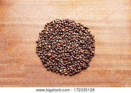 Pine nuts - small seeds of Siberian cedar pine, laid out in the form of a circle on a wooden board.