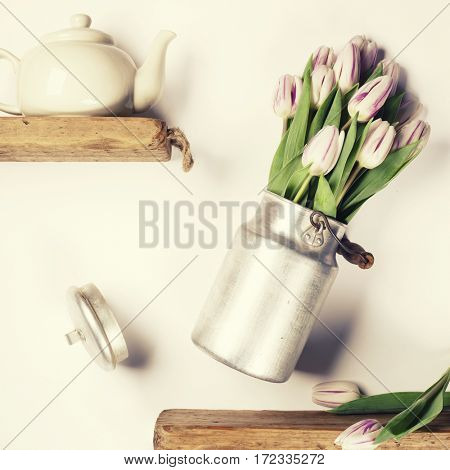 Flying pink tulips in aluminum milk can and tea cup against white wall