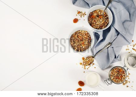 Homemade granola (with dried fruit and nuts) on white background