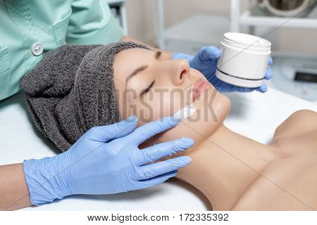 beautician applies face cream on the beautiful young woman in Spa salon. cosmetic procedure skin care. Microdermabrasion