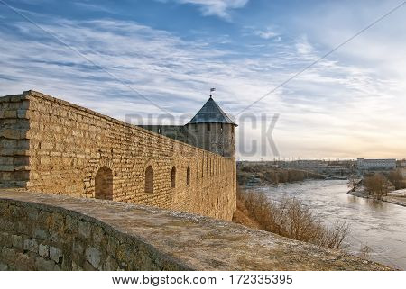 IVANGOROD, RUSSIA - JANUARY 3, 2017: View from observation deck of Ivangorod Fortress for Proviantskaya (Provision) Tower and Narva Hydroelectric Station on Narva (Narova) River