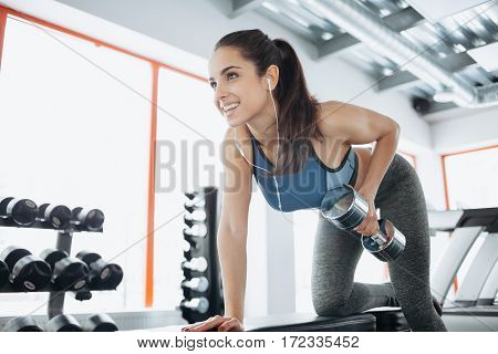 Young Beautiful Woman Doing Exercises With Dumbbell In Gym.