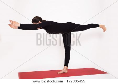 Beautiful athletic girl in a black suit doing yoga. Virabkhadrasana asana - warrior pose . Isolated on white background.