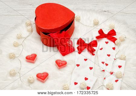 Fashion concept. Red heart shaped candles white stockings with bow red box lacy linen white fur. Garland lanterns