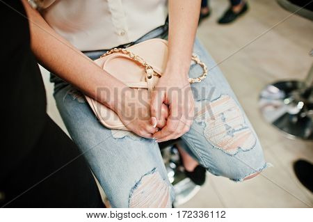 Hands Of Girl With Handbag On Ripped Jeans At Beauty Salon. Morning Of Bride.