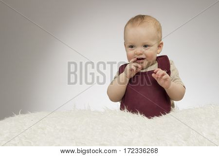 Lovely little boy smiling, sitting on the white blanket, studio shot, isolated on grey background, funny baby portrait.