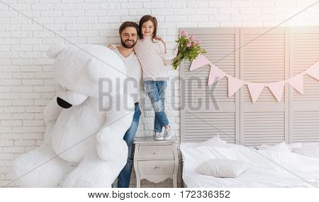 Great present. Nice handsome positive man holding a huge fluffy bear and hugging his daughter while looking at you