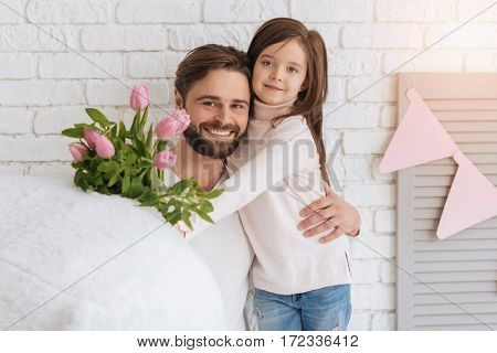 Surprise for my mom. Pretty sweet delighted girl holding a flower bouquet and hugging her father while standing near him