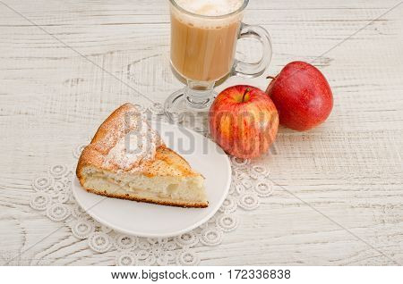Piece of apple pie cappuccino and ripe apples on a light wooden background top view