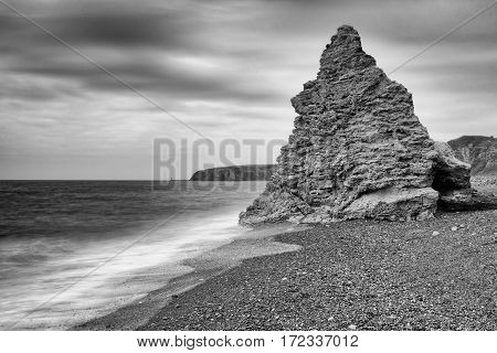 Waves lap onto a shingle beach against a magnesium limestone stack; gradually erasing the industrial legacy. Long exposure. Kiln Rock, Blast Beach, Seaham, County Durham, England UK