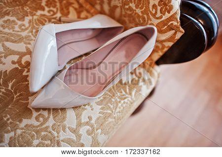 Beige Wedding Shoes For Bride On Bed.