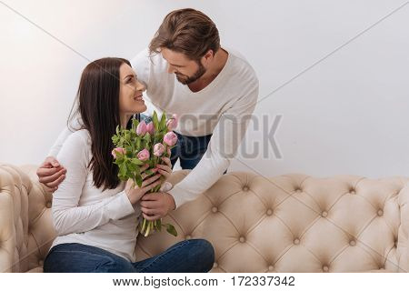 Wedding anniversary. Handsome caring positive man looking at his wife and giving her a flower bouquet while congratulating her on their wedding anniversary