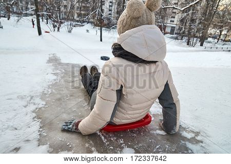 Schoolgirl is going to slide down on icy hill in the moscow yard