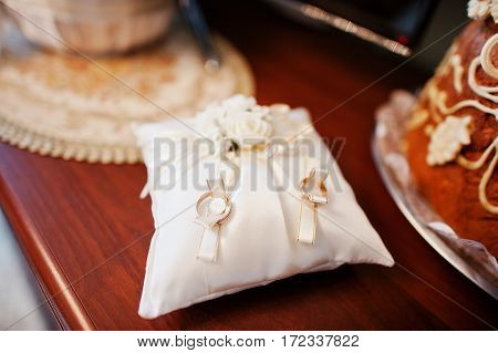 Golden Wedding Rings On Small Pillow At Ceremony.