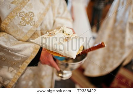Priest Hold A Small Pillow With Wedding Rings At Church Ceremony.