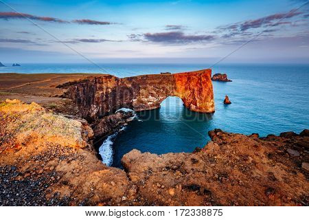 Amazing black arch of lava standing in the sea on small peninsula. Popular tourist attraction. Unusual and gorgeous scene. Location Sudurland, cape Dyrholaey, coast of Iceland, Europe. Beauty world.