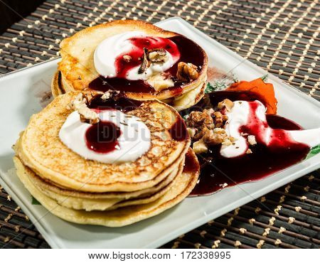 Homemade sweet pancakes with fruit jam, sour cream on a white plate. Breakfast with stack topped blueberry jam and walnuts