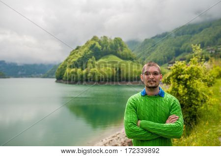 Man at beautiful emerald mountain lake Lungern in Switzerland under low clouds