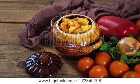 Vegetable Stew In Brown Pot With Raw Vegetables On Wooden Background