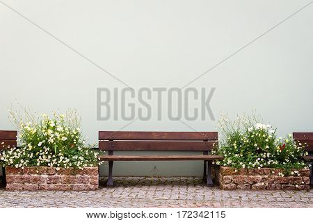 Wooden bench in front of wall and pots of flowers