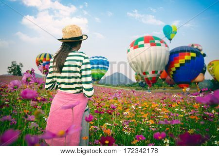 Young girl looking ballooning at cosmos flowers filed