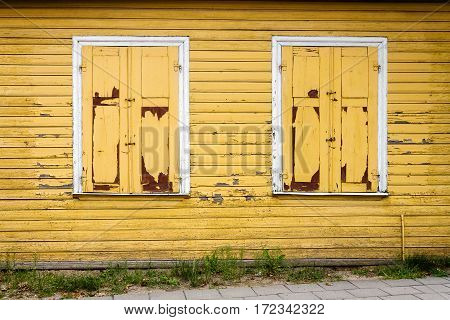 Old yellow wooden plank wall with some windows