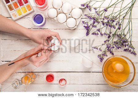 top view of female hands coloring egg on table for Easter