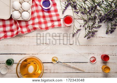 Top view of chicken eggs in box with paints and purple flowers on wooden table