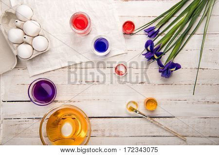 Top view of chicken eggs in box with paints and iris flowers on wooden table