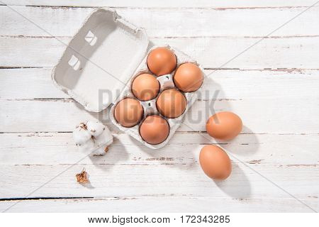 Top view of raw chicken eggs in egg box on white wooden table