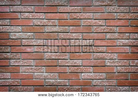 background texture of a wall made of decorative brick-red stone