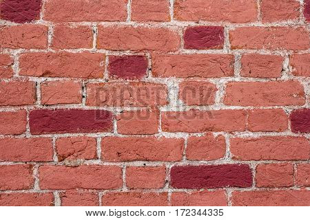 The wall of red brick. Some bricks are painted crimson red.