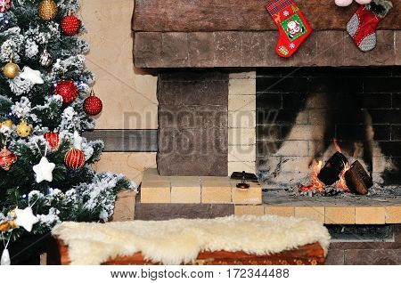 Fireplace with christmas tree and decorations in room