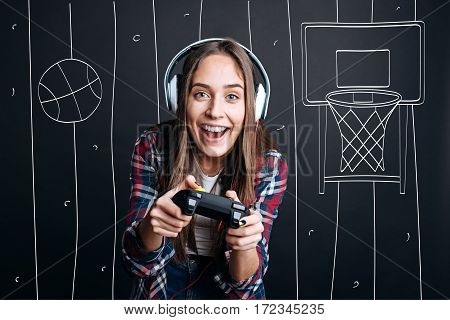 That is my hobby. Cheerful delighted smiling young woman holding game console and feeling happy while playing video games