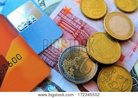 stack of multicolored credit cards and euro bills and coins scattered around close-up.