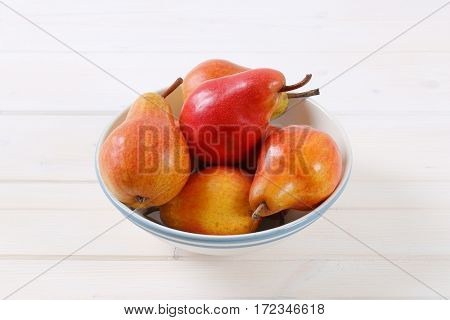 bowl of ripe red pears on white background
