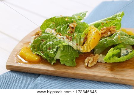 chinese cabbage salad with orange, walnuts and cheese on wooden cutting board - close up