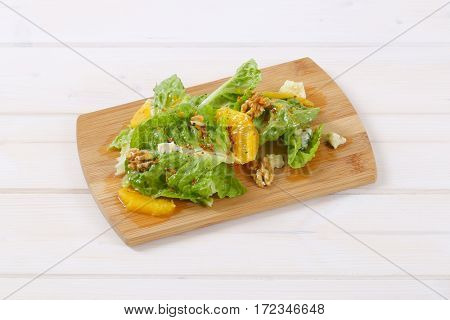 chinese cabbage salad with orange, walnuts and cheese on wooden cutting board