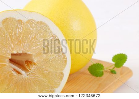 fresh ripe pomelo on wooden cutting board - close up