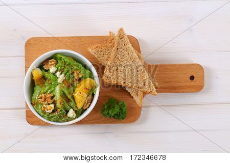 bowl of chinese cabbage salad with orange, walnuts,cheese and toast bread