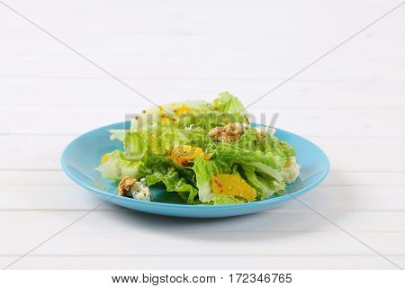 plate of chinese cabbage salad with orange, walnuts and cheese